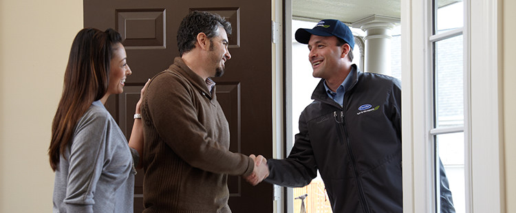 A technician greeting homeowners at their doorstep | air conditioner repair in Gainesville, FL