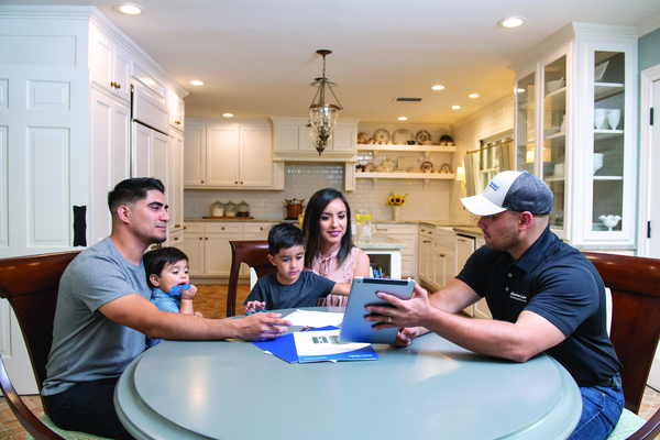 A technician explaining to homeowners | AC Repair in Gainesville, FL